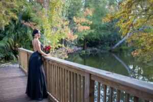 Bride by a lake in Florida wearing a delicate low back chiffon black dress