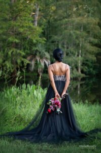 A bride looking at the lake showing the beautiful low back of her black wedding dress